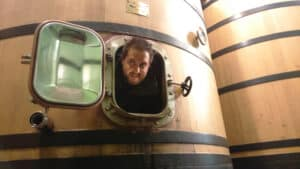A man poking his head out of a wooden fermentation vat