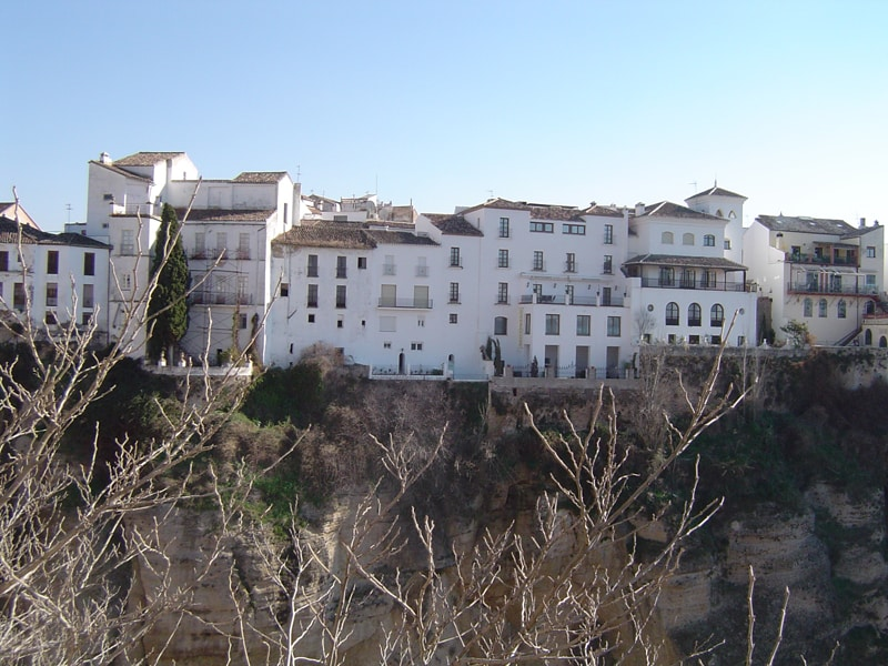 View of houses perched on cliff top in Ronda