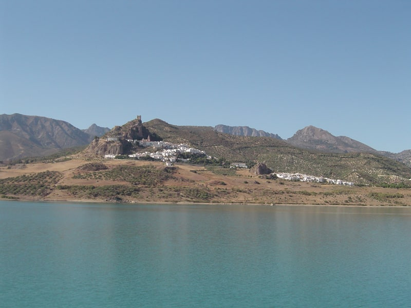 View of Zahara de la Sierra with a reservoir in the foreground and mountains in the background