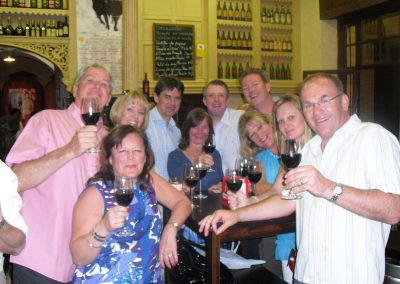 A group of people standing around a table drinking wine  during our tapas tours