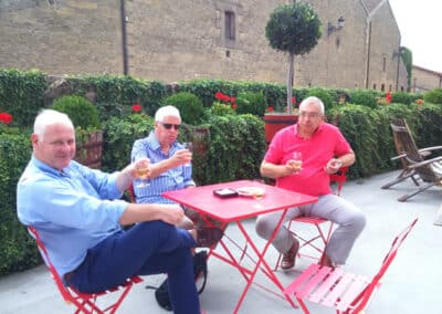A group of men sitting outside drinking white wine