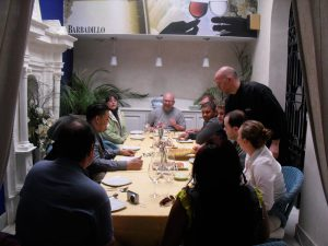 Group around a table in a restaurant talking to the chef after our cooking classes