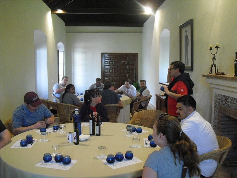 A grouup of people around two tables tasting olive oil