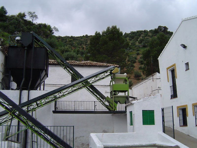 View of the outside of an olive mill with olive trees in the background
