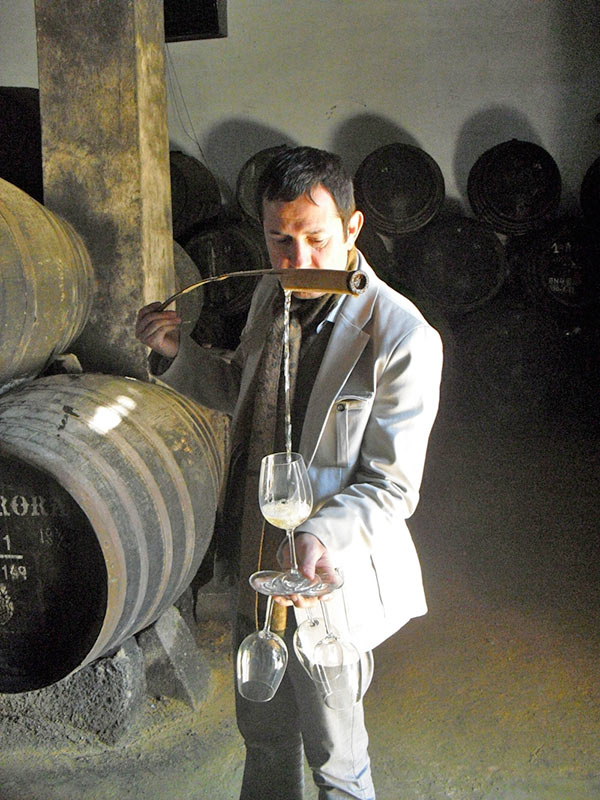 A man is pouring manzanilla sherry into a glass using a venencia