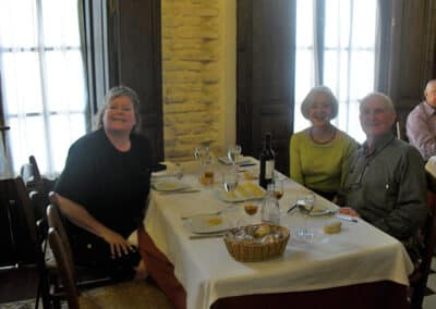A group of three people wine tasting around a table
