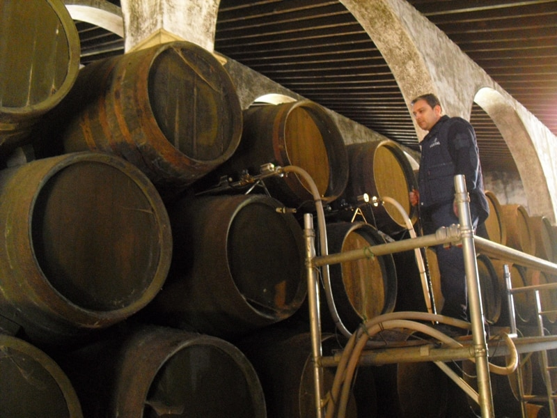 A worker in a winery who is adding or taking wine out of sherry butts